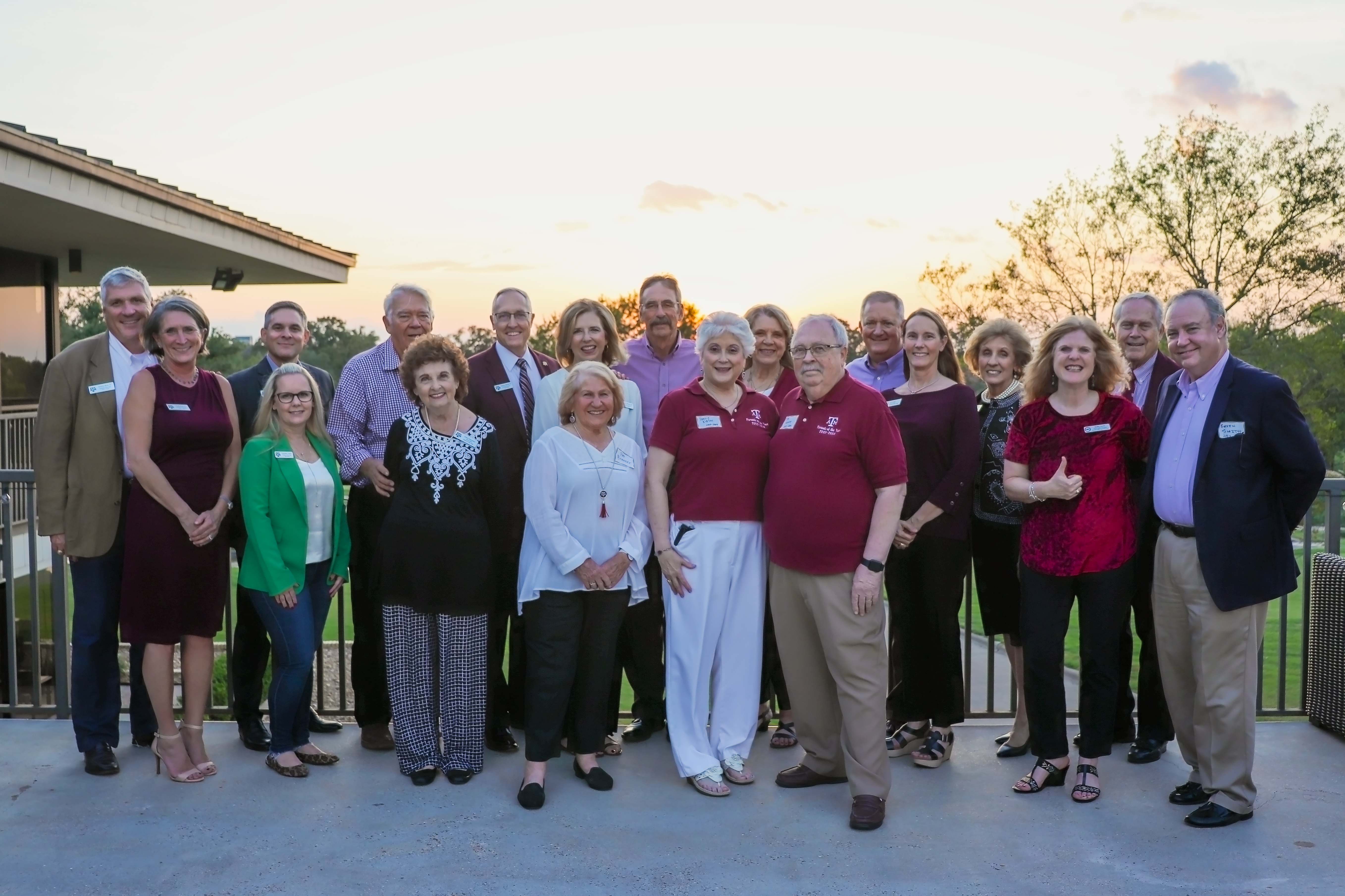 A largeo group of former parents of the year pose together for a group photo outside at sunset