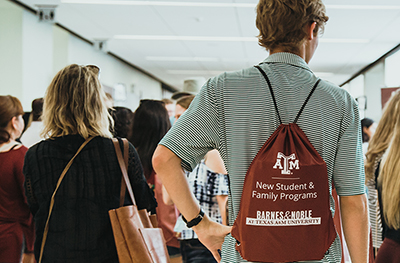 A parent and a student wearing a New Student  are seen from behind as they walk in the MSC